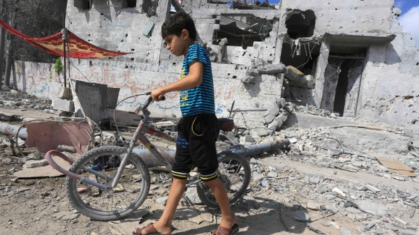 A Palestinian boy walks near the rubble of destroyed buildings as thousands of families return to their homes in Gaza