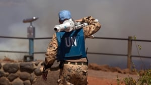 A UN peacekeeper carrying equipment as smoke rises in the background at the Syrian-Israeli border