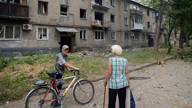 People stand near a damaged building in northern Donetsk as the US accused Russia of being 'directly involved' in fighting in Ukraine
