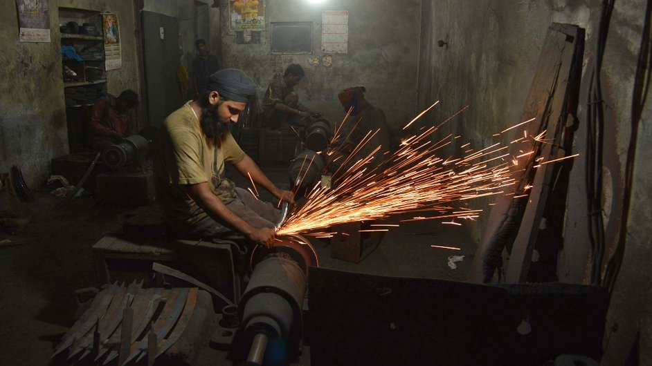 An Indian worker sharpens a sword at a workshop in Amritsar