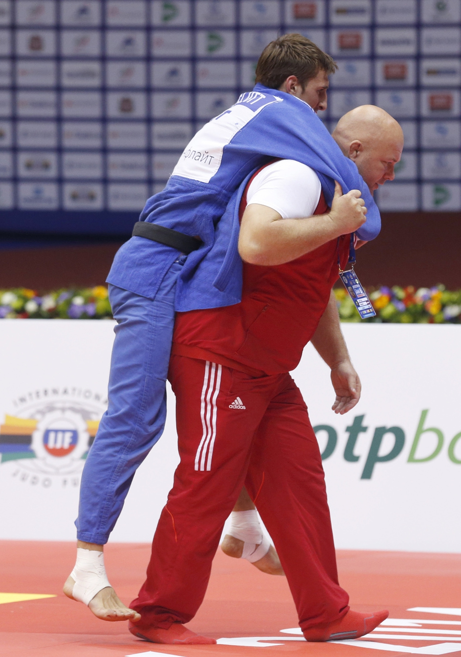 An Austrian team doctor carries judoka Marcel Ott following an injury at the Judo World Championships in Chelyabinsk, Russia