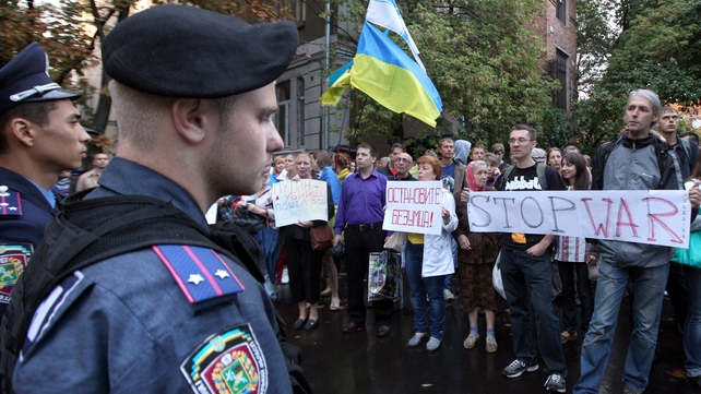 Protesters hold placards during a rally outside the Russian Consulate in Kharkiv, Ukraine