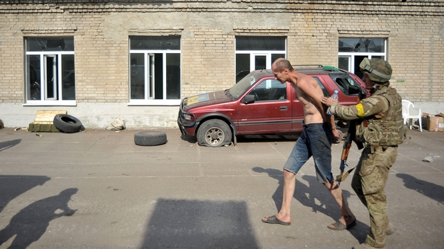 A Donbass battalion fighter holds an alleged separatist man in Ilovaisk