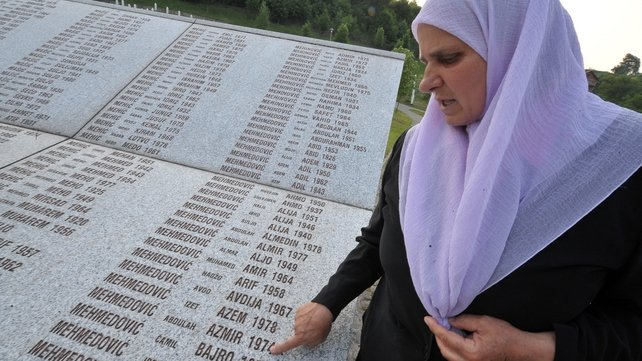 A Bosnian woman prays at a memorial for victims of the conflict