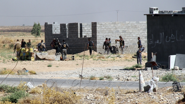 Iraqi and Turkmen fighters hold a position in the beseiged town of Amerli earlier this month