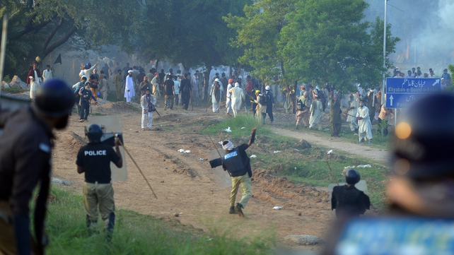 Pakistani riot police throw stones towards protesters following clashes with security forces near the prime minister's residence