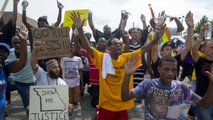 Protesters sit down in the street  during a protest over the killing of Michael Brown in Ferguson, Missouri