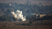 Smoke billows from the Syrian village of Quneitra amid fighting between Syrian factions