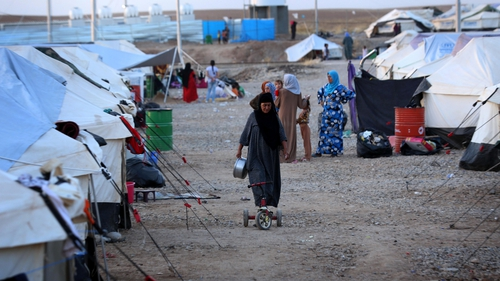 A displaced Iraqi woman walks through the Bahrka refugee camp