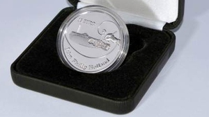 The coin features an image of the inventor's hand poised to place the final stroke of a technical drawing