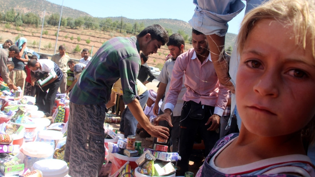 Members of the Yazidi religious minority who fled from violence in Mosul receive humanitarian aid near Dohuk city