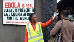 A security agent controls the temperature of a woman at the entrance of the port of Monrovia, Liberia