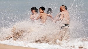 People enjoy the waves at a beach in Bali, Indonesia
