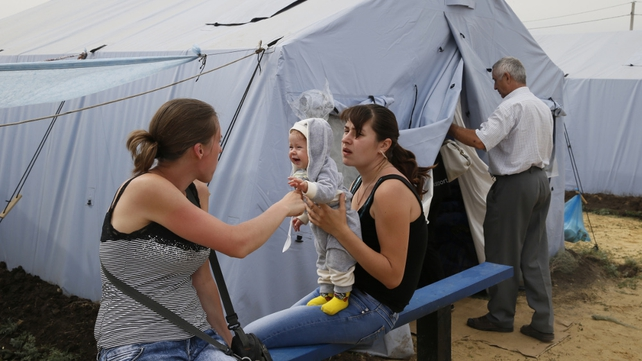 Ukrainian refugees sit near a tent at a refugee camp located about 10km from the Izvarino Russia-Ukraine border