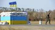 A Ukrainian fighter from the Azov Battalion walks past a checkpoint on the outskirts of Mariupol