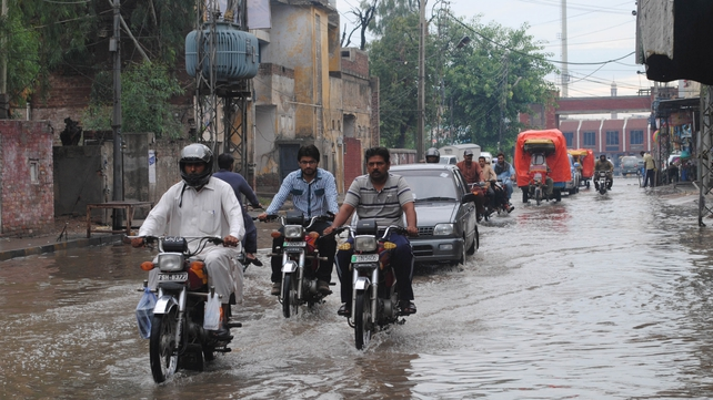 People make their way through an inundated road following heavy rains in Faisalabad
