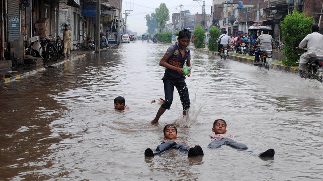 Children play in a flooded street following monsoon rainfall