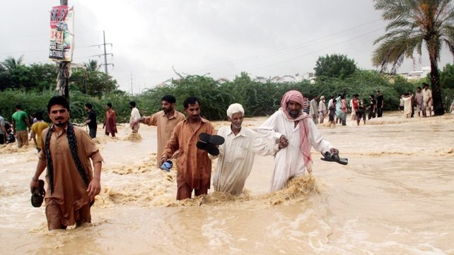 People evacuate flooded areas after heavy downpour in the country's largest city, Karachi