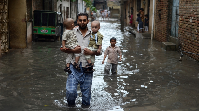 A man carries young children along a flooded street after the heavy rain in Rawalpindi