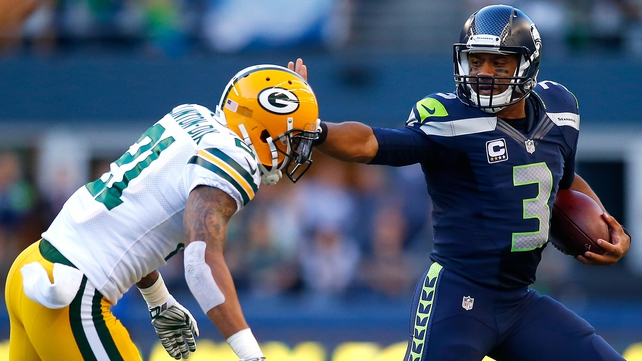 Seattle quaterback Russell Wilson (R) escapes the tackle attempt of Green Bay Packers' safety Ha Ha Clinton-Dix