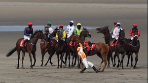 Gary Carroll struggles to keep his balance after falling off Tohugo while his masked colleagues (hoping to protect themselves from the sandy kickback) line up for the start of the O'Neills Sports Handicap