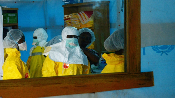 Health workers, wearing protective equipment enter a high-risk area at a hospital in Monrovia