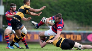 Clontarf's Ian Hirst is tackled by Darren Gallagher of Young Munster