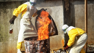 Health workers burn used protection gear at the NGO Medecins Sans Frontieres in Conakry in Guinea