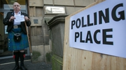 A man holds up his voting card after voting at a polling station in central Edinburgh