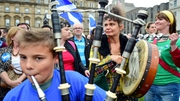 A young piper plays in George Square just a few hours before polling stations close