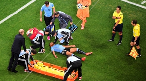 Alvaro Pereira receives treatment after a collision during the World Cup Brazil Group D match between Uruguay and England