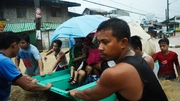 Residents are rescued by police and rescue volunteers during the floods in Manila