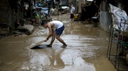 A man clears mud form his house in a suburb of Manila in the aftermath of the storm
