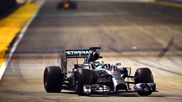 Lewis Hamilton guides his Mercedes clear of the distant blur that is the Red Bull of Sebastian Vettel at the Singapore Grand Prix
