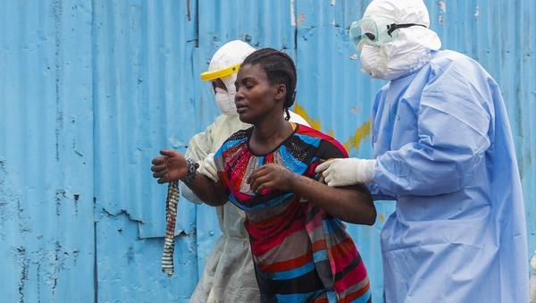Liberian nurses escort a suspected Ebola patient into a treatment centre in Monrovia, Liberia
