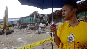 A South African woman rescued from the collapsed building looks at the rubble