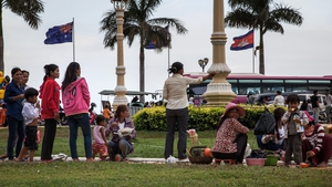 A group of street food sellers interact with Cambodian customers on the riverside in front of the Cambodian and the Australian flags in Phnom Penh