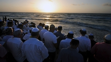 Religious Israelis stand at the edge of the Mediterranean Sea in Ashdod as they recite prayers