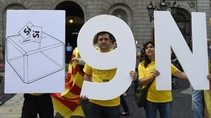 Pro-independence Catalans hold placards representing a ballot box and the date of the vote '9N'