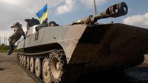 A Ukrainian serviceman jumps off a tank parked near town of Debaltseve in the Donetsk region