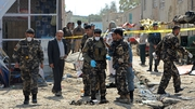 Afghan security personnel work at the site of a suicide attack near the international airport in Kabul yesterday