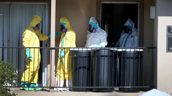 Members of a cleaning unit sanitize the apartment where the Ebola patient previously stayed