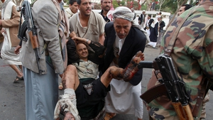 A wounded man is taken from the scene of the suicide bomb attack in Sanaa