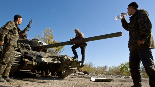 Ukrainian servicemen repair their equipment in a base camp near the town of Debaltseve in Donetsk