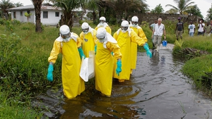 A team carries the body of an Ebola victim for burial