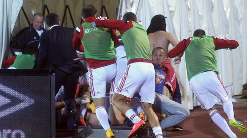 Albania's players run for cover under the stand