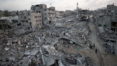 Palestinians walk through rubble of destroyed homes and buildings in Gaza