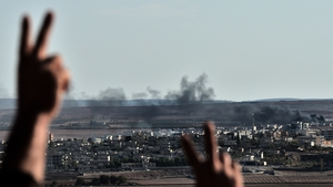 Kurdish people react as they watch smoke billowing from Kobane, as they gather upon a hill overlooking the town