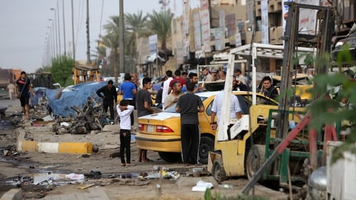 Iraqis inspect the site of the car-bomb attack in the Baghdad neighbourhood of Talbiya