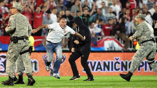 Serbian supporters invade the pitch